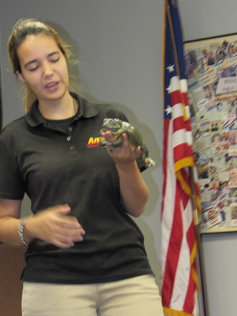 Staff photo by Cathy Spaulding<br /> A big frog clings to Vickie Arvello's hand as she displays it to kids at Muskogee Public Library.