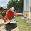 CATHY SPAULDING/Muskogee Phoenix<br /> Trevor Hamby, left, and Matt Davis of Nabholz Corp., angle a jigsaw while cutting a board at the Bank of Oklahoma downtown branch on Monday. Workers are sealing and repairing windows at the Bank of Oklahoma's downtown Muskogee branch. The branch has undergone interior and exterior renovations, window improvements and updates to drive-through teller lanes.