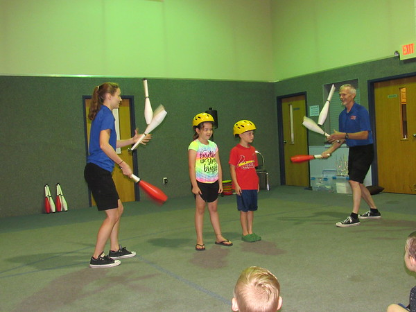 CATHY SPAULDING/Muskogee Phoenix<br /> Christa B. Hanson, left and her father Mark Hanson juggle clubs around Kayleigh Smith and Joseph Pohlmeier, both 7, during a Friday appearance at Fort Gibson United Methodist Church. The visit was sponsored by Q.B. Boydstun Library.