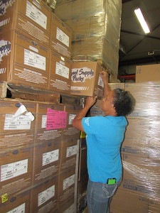 CATHY SPAULDING/Muskogee Phoenix Muskogee Public Schools Child Nutrition Services Secretary Sekora Brown pulls a box of school supplies from the MPS warehouse.