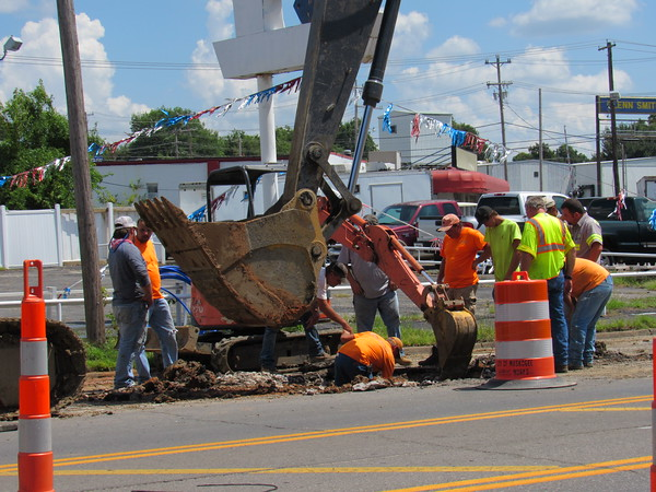 Staff photo by Cathy Spaulding<br /> Cook Construction and Crane Service employees and city workers dig into the east lane of North Main Street on Wednesday to repair a ruptured water line.