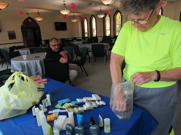 """Staff photo by Cathy Spaulding<br /> Grace Episcopal Church volunteer B.J. Charbonneau sets up toiletries in a church """"cooling shelter"""" while City of Muskogee Emergency Management Manager Mark Bolding watches. Bolding encourages churches in different parts of Muskogee to become shelters."""