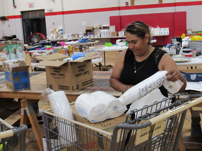 CATHY SPAULDING/Muskogee Phoenix Roseli Castro fills a shopping basket with paper products Friday at Fort Gibson's Emergency Resource Center.
