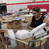 CATHY SPAULDING/Muskogee Phoenix<br /> Roseli Castro fills a shopping basket with paper products Friday at Fort Gibson's Emergency Resource Center.
