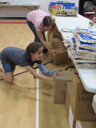 Ten-year-old Mackenzie Manegold helps her mother, Abby Manegold, push boxes under tables at the Fort Gibson Emergency Resource Center. She said they are helping because the center helped them.