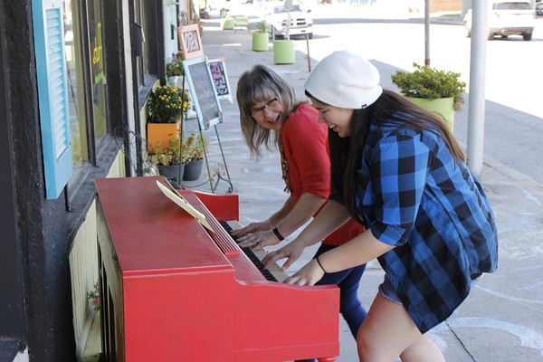 Staff photo by Harrison Grimwood<br /> Lisa LaRue-Baker, left, and Millisa Henderson play together Friday morning on the street piano placed outside a Main Street business in downtown Muskogee.