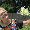 Staff photo by Cathy Spaulding<br /> Susan Asquith admires flowers growing in her backyard. She recently completed a term as Muskogee Garden Club president.