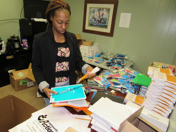 Staff photo by Cathy Spaulding<br /> Raven Bolden, an intern with Muskogee County Community Action Foundation, gathers school supplies that will be given away Aug. 1 and 3 to eligible families. The supplies are for children enrolled in kindergarten through fifth grade.