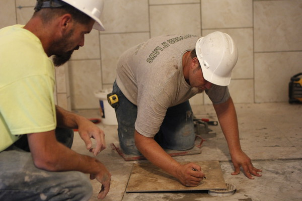 Staff photo by Harrison Grimwood<br /> John Ussery marks a piece of tile Friday so Chris London can cut it to fit a drain at the new Muskogee Little Theatre, a project that many hope will spur downtown revitalization efforts.