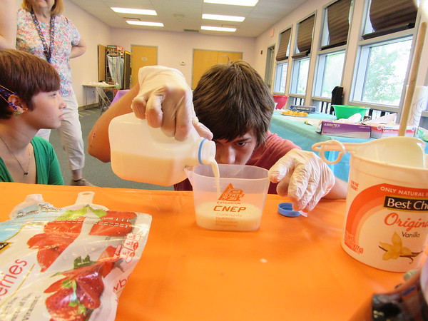 CATHY SPAULDING/Muskogee Phoenix<br /> Trystan Turpin, 15, gets to eye-level as he measures milk for a strawberry-banana smoothie. He joined seven other teens at a cooking class at Q.B. Boydstun Library.