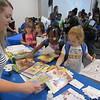 CATHY SPAULDING/Muskogee Phoenix<br /> Christine Hamby of United Methodist Church Circle of Care shows Caroline Jones, right, and others a variety of coloring books and reading books. Scores of youngsters celebrated the end of the Dream Team Summer Learning program Tuesday at the Dr. Martin Luther King Jr. Community Center.