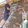 Staff photo by Mike Elswick<br /> Butch Gale, left, and Billy Grimes, connect wires for satellite television and internet service. Part of the job requires working in attics, where temperatures can exceed well above the 100-degree mark.