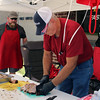 Photo by Travis Sloat<br /> JT Burns chops up smoked pork Saturday as his son, Bryan Burns, watches at Eufaula's Whole Hawg Festival.