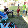 Photo by Travis Sloat<br /> Ava Miller, 4, and Maddox Miller, 10, do their best to toss rings onto pop bottles at the Eufaula festival to win a rabbit.