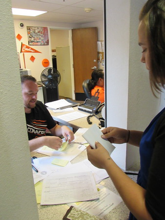 Staff photo by Cathy Spaulding<br /> Connors State College Assistant Bursar Trent Todd, left, exchanges papers with student Justina Read of Warner. Read said she is concerned about how her financial aid will keep up with rising tuition and fees.