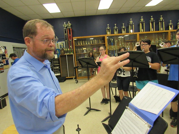 Staff photo by Cathy Spaulding<br /> Veteran Checotah Band Director Jimmy Davis directs students in a scale drill Monday. With trophies loading his classroom, Davis is a 2017 inductee into the Oklahoma Bandmasters Hall of Fame.