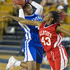 Phoenix special photo by Von Castor<br /> Muskogee's Aaliyah Wilson, left, gets fouled on her way to the basket during Wednesday's All-State Large School Girls basketball game at ORU's Mabee Center. Wilson, who played for the East squad, finished the game with nine points as the East beat the West 73-62.