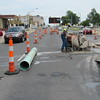 Staff photo by Cathy Spaulding<br /> Traffic on West Okmulgee Avenue passes both sides of city workers cutting into the pavement Wednesday afternoon. Public Works Department crews dug into a sewer line near the 800 block of West Okmulgee to see what repairs are needed. A sanitary sewer line had failed in the vicinity of a storm sewer line, causing a sinkhole. The sanitary line was repaired, and the city is working to repair the storm sewer.