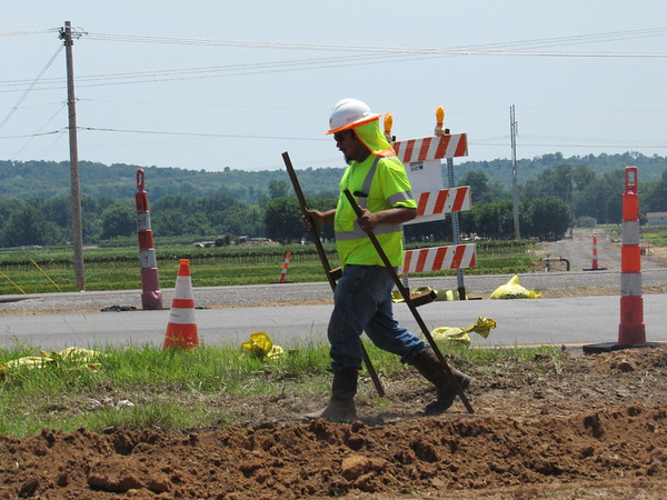 CATHY SPAULDING/Muskogee Phoenix<br /> A construction worker moves stakes past what used to be a crossing for the Oklahoma 10 exit off U.S. 62. The Oklahoma Department of Transportation moved the Oklahoma 10 exit west to the intersection of Georgetown Road and U.S. 62. ODOT closed the old Oklahoma 10 exit.
