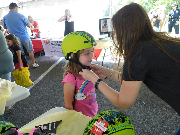 """KENTON BROOKS/Muskogee Phoenix<br /> Emaline Hill of Tahlequah, left, gets fitted with a new bicycle helmet by Tisha Barnes of the Warren Clinic on Saturday at the Saint Francis Hospital Muskogee Summer Safety Fest. Emaline said she learned that """"you should always wear a helmet because if you don't, you could crack your head open."""""""