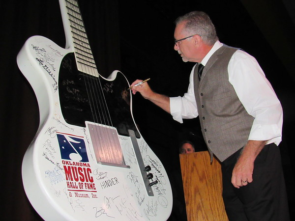 SPAULDING/Muskogee Phoenix<br /> Gospel singer/songwriter Dennis Jernigan signs an Oklahoma Music Hall of Fame autograph guitar Saturday night at his induction into the hall of fame.