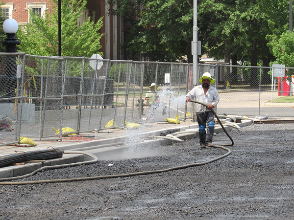 CATHY SPAULDING/Muskogee Phoenix<br /> Tony Garcia of Easky Construction hoses a gravel base on Monday afternoon to make it easier to lay concrete. Fifth Street has been closed between Broadway and Okmulgee Avenue, in front of the United States Courthouse. According to city of Muskogee records, the General Services Administration sought to close the street to increase security and create a more park-like setting. The street remains open for pedestrian use.