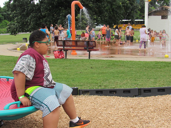 CATHY SPAULDING/Muskogee Phoenix<br /> Camp Bennett camper Anthony Banks bides his time bouncing in the Elliott Park playground set while other campers enjoy the splash pad Tuesday.