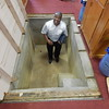 Staff photo by Mark Hughes<br /> The Rev. Gary Hall Sr. stands in the concrete baptistry of his church, Mount Calvary Baptist Church. The two-story building sits on a hill, with the first floor at street level. To save space, the baptistry was built under the pulpit. The aging church will be closed after Sunday's service and be demolished next month.