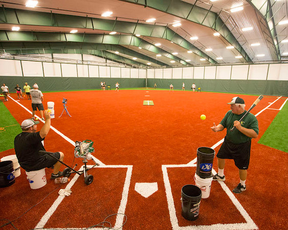 Special photo by Von Castor<br /> Muskogee assistant softball coach Don Yates, right, hits fungos while head coach Keith Coleman, seated, uses the machine as the Lady Roughers held their first fall practice of the season inside the new $2.6 million indoor facility on Thursday.