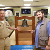 Staff photo by Mark Hughes<br /> Cmdr. Keith Campbell and Brent Trout, the director of Muskogee's War Memorial Park, welcome the newest addition to its museum — an oak stand that holds the bell belonging to the World War II submarine USS Batfish. Sailors from Campbell's unit, Central Naval Center for Navy Aviation Technical Training detachment, spent around 100 hours of their free time making the stand.