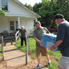 "Staff photo by Cathy Spaulding<br /> John Lawson, left, watches while his son, Jeremy Lawson, center, and Mark Hudson carry a 5,000 BTU air conditioner to his house. John Lawson said he had needed the air conditioner for ""quite some time."""