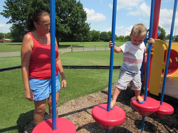 CATHY SPAULDING/Muskogee Phoenix<br /> Dee Dee Stevenson of Fort Gibson watches her 3-year-old grandson Greyson Pitts make his way across hanging platforms at Civitan Park's playground. Stevenson said that six months ago, the boy was afraid to go on the platforms.