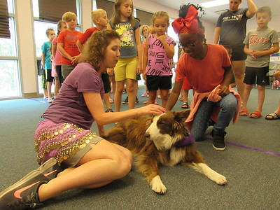 CATHY SPAULDING/Muskogee Phoenix Denise Gard, a storyteller from Colorado, brought two border collies to Q.B. Boydstun Library on Friday to help the library celebrate the conclusion of its 2018 Summer Reading Program. Gard, left, lets McKenzie Colbert, 9, pet Sienna, one of the two border collies she brought.
