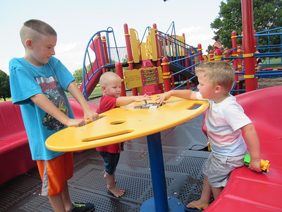 CATHY SPAULDING/Muskogee Phoenix Youngsters found several ways to have fun in Monday afternoon's warm sun at Civitan Park Playground. A tic-tac-toe game entices A.J. Pickett, 2, center, and Greyson Pitts, 3, right, while Leon Travis, 8, watches.
