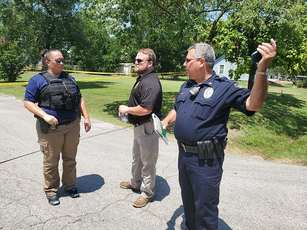 CHESLEY<br /> OXENDINE/Muskogee Phoenix<br /> Two Oklahoma State Bureau of Investigation agents who asked not to be identified speak with Haskell Police Chief Michael Keene (right) Keene requested OSBI take over the investigation of a shootout in Haskell on Tuesday morning.