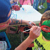 Staff photo by Cathy Spaulding<br /> Amber Watson paints a red Ninja Turtle mask on 9-year-old Eli Fausett's face Monday at the Timothy Baptist Church Independence Day celebration. Watson said she painted at least 30 faces before dark.