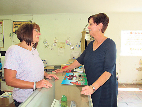 Staff photo by Cathy Spaulding<br /> Fort Gibson Chamber of Commerce board president Denise Bain, left, visits with Sue Godwin days before Godwin's departure as Chamber executive director.