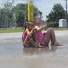 Staff photo by Cathy Spaulding<br /> Sisters Scout Sapulpa, left, and Payton Green rest under an umbrella of water.