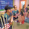 Staff photo by Mike Elswick<br /> Alyson Madewell and mother-in-law Mickey Madewell manned the flag and T-shirt concession at Muskogee First Assembly of God during the congregation's community-wide Independence Day celebration. They said sales of both shirts and flags were brisk.