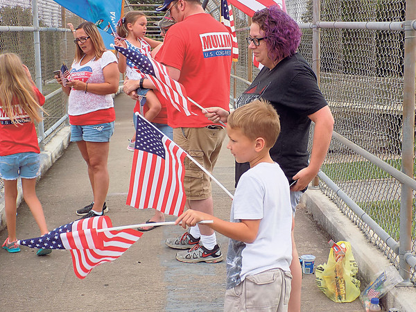 Staff photo by Mike Elswick<br /> Camden Minor and his mother, Elizabeth Barrington, were among a group waving flags to motorists below from the pedestrian walkway over Peak Boulevard on Tuesday.