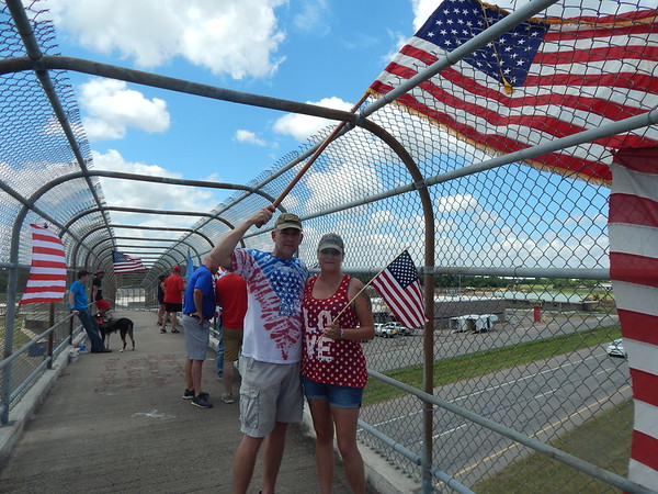 "ABIGAIL HALL/Muskogee Phoenix<br /> Deshayn and Eva Wilson celebrate the Fourth of July by hosting ""Raise the Flag,"" where they invite locals to wave flags to oncoming traffic on East Peak Boulevard. The couple has been doing this for four years."