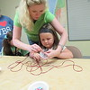 Staff photo by Cathy Spaulding<br /> Robin Stanley helps Olivia Peevehouse, 5, weave an Egyptian basket during Grandview Baptist Church's vacation Bible School. The church used Moses and Egypt as its theme.