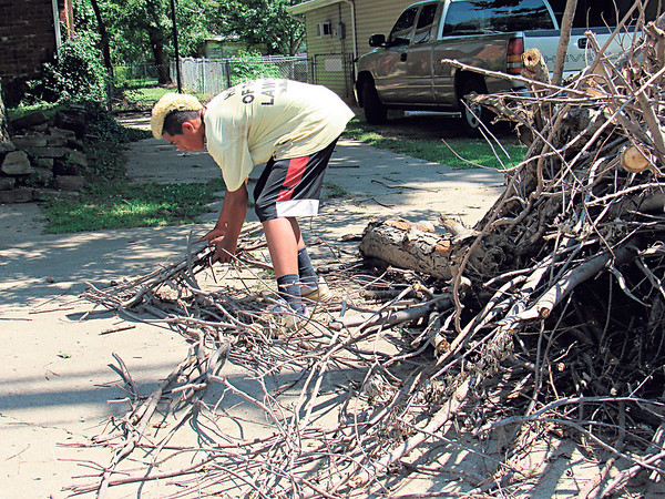 Staff photo by Cathy Spaulding<br /> Claude Sheppard of C4's Lawns and Landscaping picks up branches from a Fort Gibson homeowner's tree that fell in a recent storm.