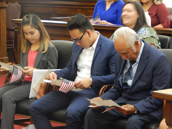 CHESLEY OXENDINE/Muskogee Phoenix<br /> From left, Sengkea Sdok, Ivan Bao Nguyen, and Jose Rogelio Hernandez Silas inspect their naturalization certificates.