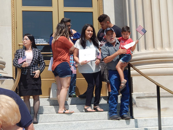 CHESLEY OXENDINE/Muskogee Phoenix<br /> Newly naturalized citizens — along with their friends and family — emerge from the federal courthouse after a Friday morning ceremony.