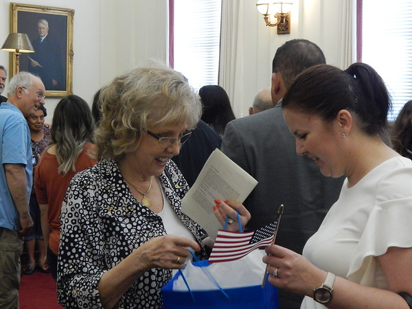 CHESLEY OXENDINE/Muskogee Phoenix<br /> Daughters of the American Revolution representative Delia Brown, left, gives a gift bag that includes an American Flag to new citizen Karolina Boulet.