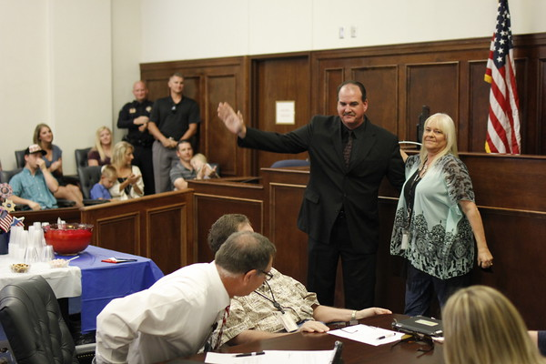 Staff photo by Harrison Grimwood<br /> Wagoner County Sheriff Chris Elliott, center, greets a crowded courtroom with his wife, Judy Elliott, after an associate district judge swore him into office Thursday.