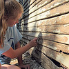 Staff photo by Cathy Spaulding<br /> Maddie Armstrong, 13, peels paint from a shed as part of Mission Muskogee. One hundred youth volunteers are working various projects through Tuesday.