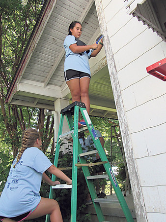 Staff photo by Cathy Spaulding<br /> Avery Lohmann, 12, holds a ladder for Kameryn Walker, 12, as she scrapes paint from a Muskogee home. The youths are volunteering for Mission Muskogee.