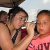 CATHY SPAULDING/Muskogee Phoenix<br /> Britteny Cuevas paints Zoe Parrish's face during the Okie Art Fest. Cuevas said she liked how the festival encouraged local artists.